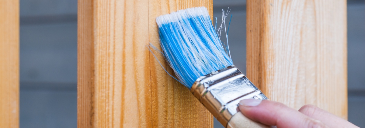 A paint brush puts a fresh coat of finish on a fence.